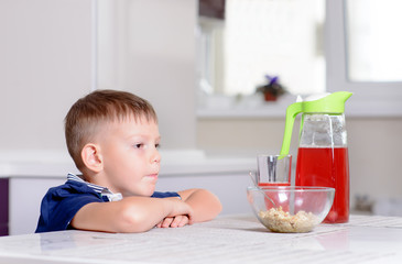 Boy at Kitchen Table with Bowl of Cereal and Juice