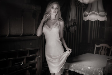Sexy blonde woman in vintage room.
