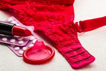 Pills, lipstick and condom with lace lingerie.