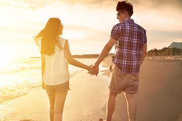 young couple enjoying a beach walk at sunset