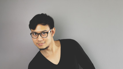 A man with eyeglasses is looking at the camera in funny pose.