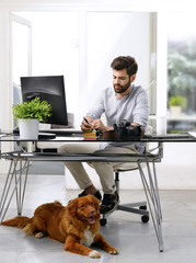 Young creative with his dog at office