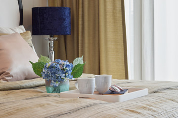 decorative tray of tea cup and book in stylish bedroom interior