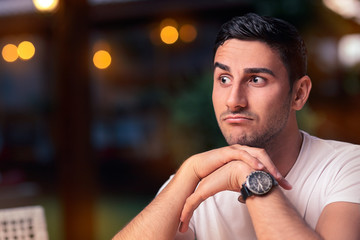 Surprised Young Man Sitting in a Restaurant