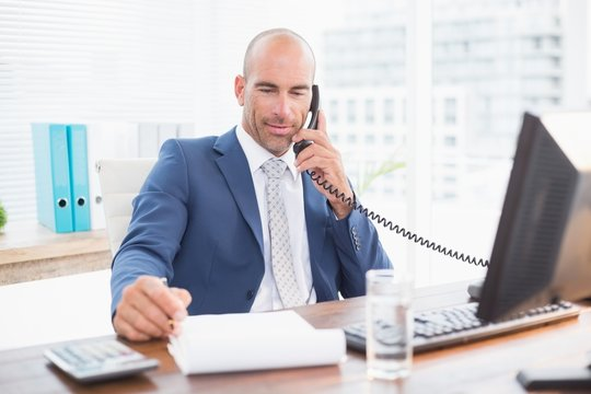 Businessman on the phone and writing notes