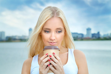young blonde woman drinking coffee on a summer morning by the river with views of the city. Lifestyle