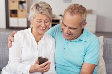 älteres paar schaut gemeinsam auf eine sms am mobiltelefon