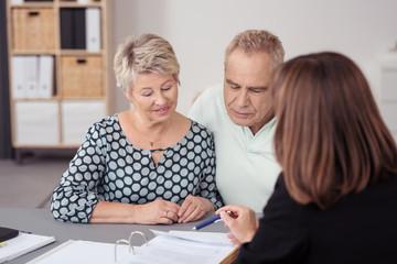 beraterin erklärt einem älteren paar die formulare
