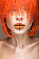 Beautiful girl in an orange wig cosplay style with bright creative lips. Art beauty image. Portrait shot in the studio.