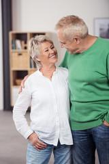 lachendes älteres paar in ihrem wohnzimmer