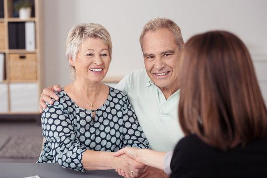 senioren-ehepaar schüttelt beraterin die hand