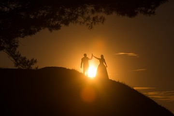Silhouettes of wedding couple standing on hill.