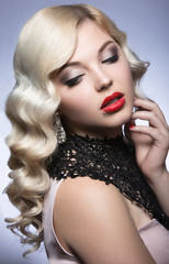 Beautiful blonde in a Hollywood manner with curls, red lips and lace dress. Beauty face. Picture taken in the studio on a white background.
