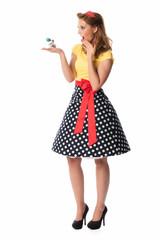 Pinup Girl hält Parfümzerstäuber und staunt