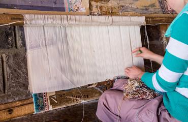 woman making carpet on loom