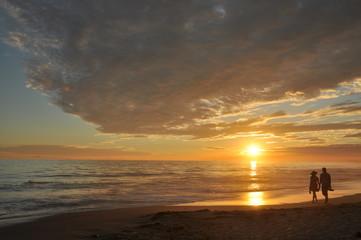 夕日の沈む海岸を歩く恋人たち
