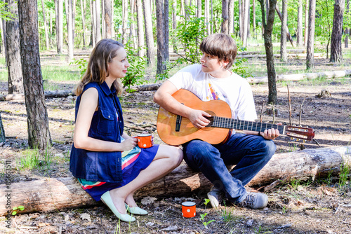 Portrait Of Young Loving Happy Couple With Guitar In Forest Cute Girl And Man Singing