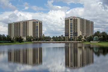Two Building's Reflections - Two Tall Buldings Surrounded by Large White Puffy Clouds Rest On the Bank Of a Smooth Reflective Lake