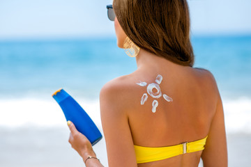 Woman using sun cream on the beach