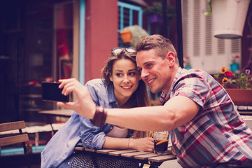 Young happy couple in the cafe taking selfie