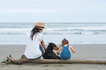 砂浜に座る親子と犬