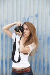 Young woman taking photograph with digital camera