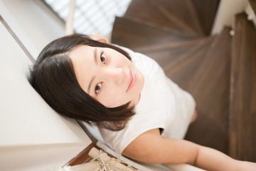 階段で笑みを浮かべて見る女性モデル