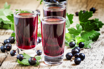 Fresh black currant juice with berries in glasses on an old wood
