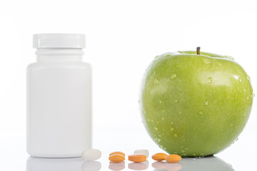Natural green apple and various colored pills on white
