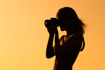 Silhouette of a woman photographing