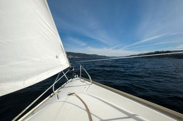 Proa de un velero navegando sobre la costa gallega del Océano Atlántico un día soleado
