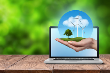 Fototapete - Wind turbines with tree in female hand in laptop