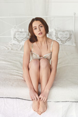 seductive girl sitting on white bed hugging her legs hands