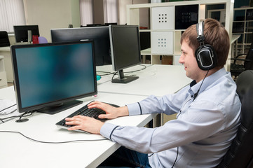 Young handsome man wearing earphones with computer in the office.
