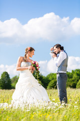 Wedding couple taking pictures on meadow
