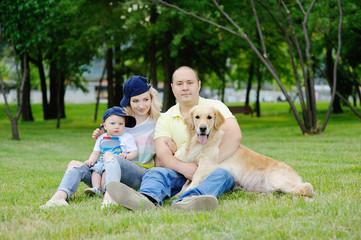 family with a dog retriever on the grass