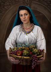 Old World image of european woman carrying basket of fruit wearing attire from the past.  Photo was created to appear like an old world painting.