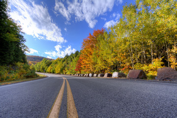 Autumn daytime view of a mountain road in Lake George, NY on Prospect Mountain, Adirondack State Park, with trees changing color.