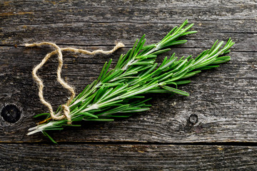 Fresh rosemary spring on gray wooden table, top view