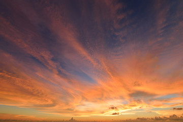 sunset sky with clouds explosion and golden light at ocean ,long