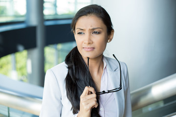 Closeup portrait, woman leader in gray suit with black glasses under chin thinking hard, cogitative, needing to make tough decisions, isolated indoors office background