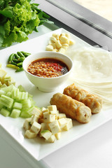 pork and vegetable vietnamese and spicy sauce in white ceramic dish