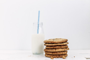 Stack of cookies and bottle of milk with a straw