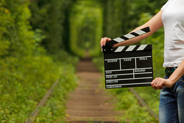 Girl holding clapper board in her hands. tunnel of love