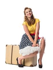 Junge Frau sitzt auf einem Koffer und wartet