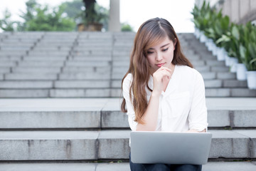 Asian beautiful female student using laptop in campus