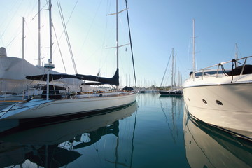 reflections of super yachts and motor power boats in a marina