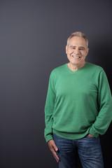 lächelnder älterer mann vor grauer wand