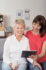 mutter und tochter schauen zusammen auf tablet-pc