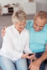 älteres ehepaar schaut gemeinsam auf mobiltelefon